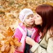 Young mother and her toddler girl have fun in autumn — Stock Photo #12186159