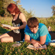 Two students read textbook against summer nature. — Stock Photo #12186370