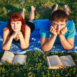 Royalty-Free Stock Photo: Two students read textbook against summer nature.