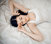 Closeup portrait of a cute young woman sleeping on the bed — Stock Photo