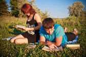 Two students read textbook against summer nature. — Stock Photo