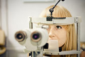 Optometry concept - pretty young woman having her eyes examined by an eye doctor on a slit lamp — Stock Photo
