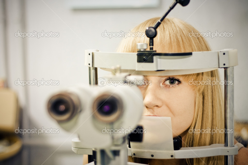 Optometry concept - pretty young woman having her eyes examined by an eye doctor on a slit lamp   Stock Photo #12187032