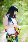 Beautiful pregnant woman relaxing outside in the park Beautiful pregnant woman relaxing outside in the park — Stock Photo