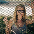 The beautiful girl wearing spectacles behind a lattice — Stock Photo
