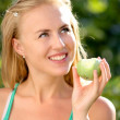 Portrait of young beautiful happy smiling woman with green apple, outdoors  — Stock Photo #25411343
