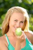 Portrait of young beautiful happy smiling woman with green apple, outdoors — Stock Photo