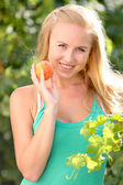 Portrait of young beautiful happy smiling woman with peach, outdoors — Stock Photo