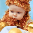 Portrait of beautiful newborn baby in hat of tinsel — Stock Photo