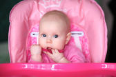 Cheerful baby child eats itself with a spoon — Stock Photo