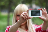 Pretty young blonde photographer in green park — 图库照片