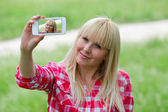 Pretty young blonde photographer in green park — Stock Photo