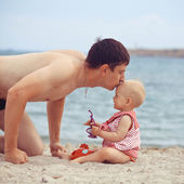 Father kisses the daughter on the sea — Stock Photo