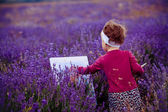 The little girl draws a picture in a lavandovy field — Stock Photo