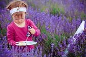 The little girl draws a picture in a lavandovy field — Stock fotografie