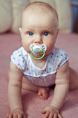 Baby sucks a pacifier — Stock Photo