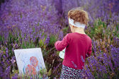Girl draws a picture in a lavandovy field — Photo