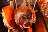 Smoked ham, meat hanging in the smokehouse — Stock Photo