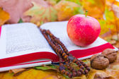 Rosary on the Bible with apple and nuts — Stock Photo