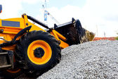 A bulldozer picking up gravel on jobsite. — Stock Photo
