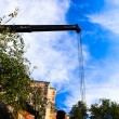 Mobile crane with risen boom into a blue sky — Stock Photo