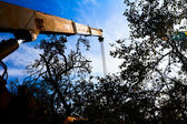 Mobile crane with risen boom into a blue sky — Stockfoto