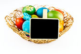 Easter eggs with black board, isoalted on white — Stock Photo