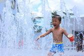Un ragazzo asiatico schizzata di fontana d'acqua in estate — Foto Stock