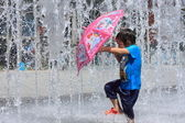 A asian kid splashed by water fountain in summer — Stock Photo
