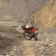 Stock Photo: Red Kawasaki motorcycle on a mountain road in the Himalayas in Nepal