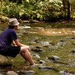 Stock Photo: Teen sitting on river rocks