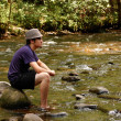 Stock Photo: Teen sitting on river rocks, side view