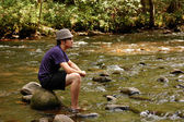 Teen sitting on river rocks, side view — Stock Photo