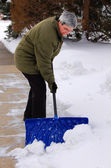 Middle aged woman shoveling — Stock Photo