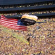 US Airborne parachutist travels past crowd at UM-MSU gam — Stock Photo #12193818