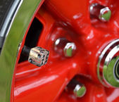 Tire red hubcab with dice — Stock Photo