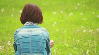 Girl sitting on green grass — Stock Video