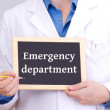 Doctor shows information on blackboard: emergency department — Stock Photo #13610549