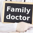 Doctor shows information on blackboard: family doctor — Stock Photo #13967956