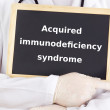 Doctor shows information on blackboard: acquired immunodeficiency syndrome — Stock Photo