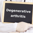 Stock Photo: Doctor shows information: degenerative arthritis