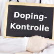 Doctor shows information on blackboard: doping test — Stock Photo