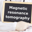 Doctor shows information: magnetic resonance tomography — Stock Photo #13969339