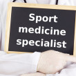 Doctor shows information: sport medicine specialist — Stock Photo