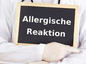 Doctor shows information on blackboard: allergic reaction — Stock Photo