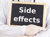 Doctor shows information on blackboard: side effects — Stockfoto