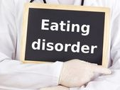 Doctor shows information on blackboard: eating disorder — Stock Photo