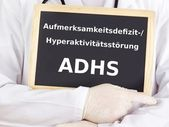 Doctor shows information on blackboard: adhs — Stock Photo