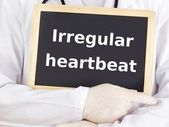 Doctor shows information: irregular heartbeat — Photo
