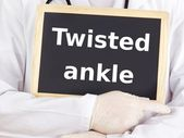 Doctor shows information on blackboard: twisted ankle — Stock Photo